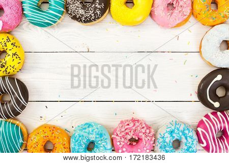 Colorful Donuts On Light Wooden Background