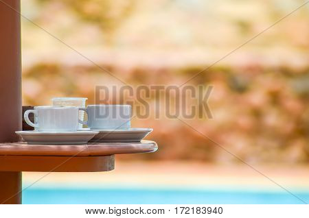 Two cups of coffee on the table near the pool