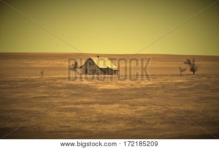 Lone abandoned and vintage home on the open windswept prairie grassland with a sepia finish