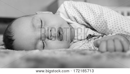 Cute newborn baby sleeping on the bed black and white