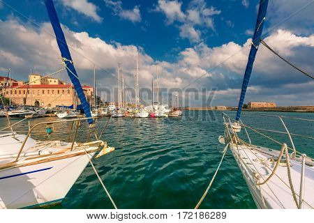 Venetian shipyards, and fishing boats in old harbour of Chania in cloudy summer morning, Crete, Greece