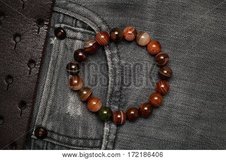 Bracelet on the arm on the background of jeans, top view