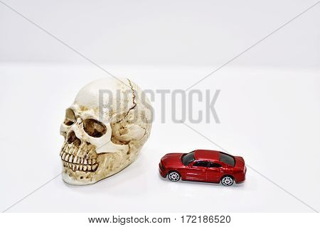 Abstract composition of car crash. Decorative Skull and small car model.