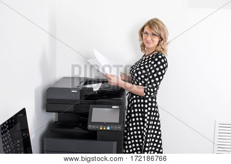 Young beautiful woman in a black polka-dot dress making copies in the office