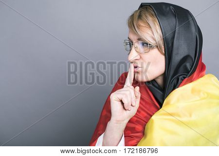 Germany Woman requires silence. Young beautiful blonde model has put forefinger to lips as sign of silence, isolated on gray background