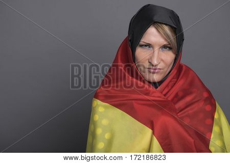 Young beautiful woman wrapped in the German flag