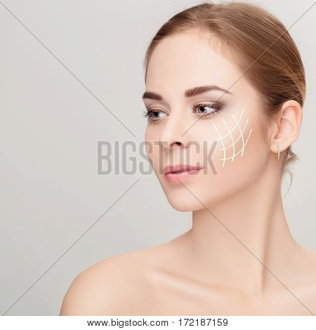 Spa portrait of attractive woman with arrows on her face over grey background. Face lifting concept. Plastic surgery treatment, medicine
