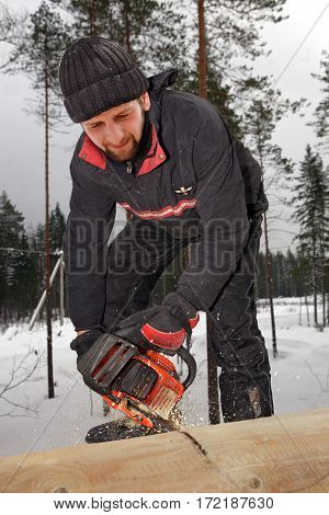 Leningrad Region Russia - February 2 2010: builder worker at wooden works cutting wood timber with portable saw.