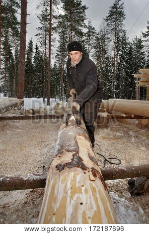Leningrad Region Russia - February 2 2010: The process of peeling and debarking of wood Worker the logs are hand peeled using a drawknife.