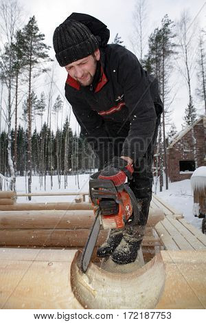 Leningrad Region Russia - February 2 2010: Builder handles log using chainsaw He cut out round saddle notch.