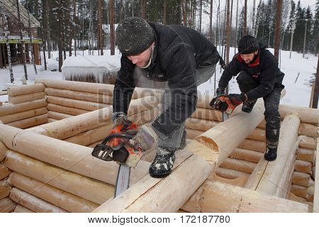 Leningrad Region Russia - February 2 2010: Construction log house in winter outdoors workers make notches on logs using chainsaws.