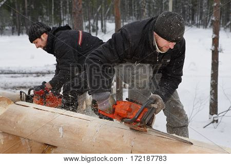 Leningrad Region Russia - February 2 2010: Building log cabin in winter outdoors loggers make notches on logs using chainsaws.