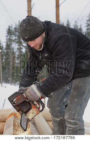 Leningrad Region Russia - February 2 2010: Processing logs Worker cuts out the lateral groove and corner notches using chain saw.