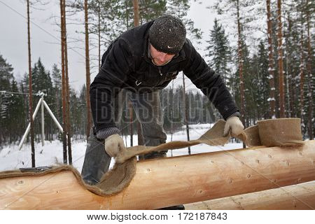 Leningrad Region Russia - February 2 2010: The heat insulator between the logs worker install jute insulation tape.