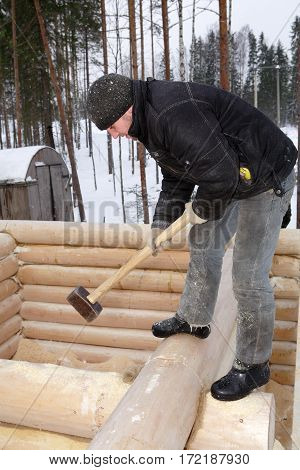 Leningrad Region Russia - February 2 2010: Handyman aligns a wall with a sledge hammer