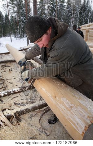 Leningrad Region Russia - February 2 2010: Woodworker Planes timber using an electric planer.