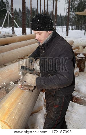 Leningrad Region Russia - February 2 2010: Processing logs for building log removing the bark using a planing machine.