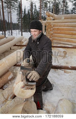 Leningrad Region Russia - February 2 2010: Young worker removes the bark from a log using the electric planer.