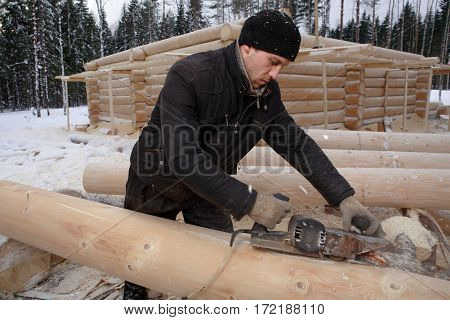 Leningrad Region Russia - February 2 2010: Construction of a log cabin planing of a log by an electric jack-plane.