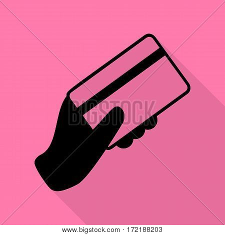 Hand holding a credit card. Black icon with flat style shadow path on pink background.