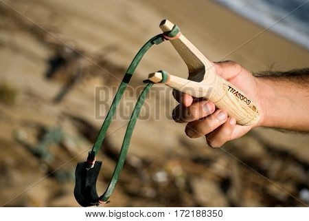 Close up Hand of a Man with Stone Shooter Stick with latter Thassos, Greece.