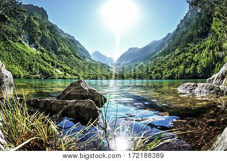 ancient rocks on the shore of beautiful mountain lake on a background of the majestic mountains