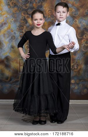 Young boy and girl are dancing on the studio wall background