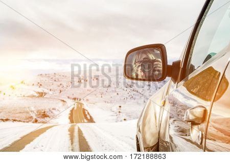 Beautiful girl sitting in an SUV riding in the mountains, in the reflection of the side mirrors photographs on the camera