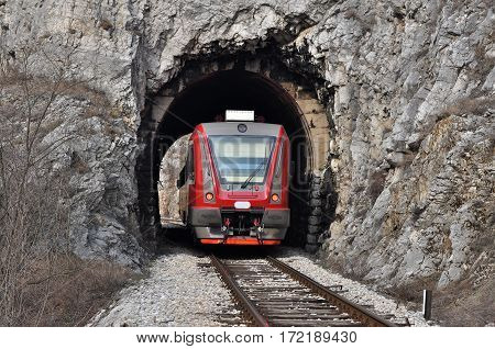 The train on the railway line comes from a small tunnel, New train on old railway.