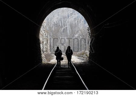 Two women walk the railway and get out from tunnel. Light on the end of the tunnel