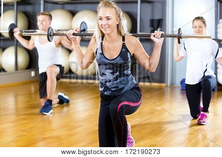 Full length of smiling young woman lifting barbell rod with friends in gym