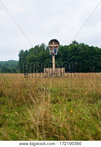 Old traditional wooden crucifix in the field in the Carpathian region in Ukraine.