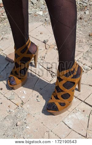 Woman's feet in high heel sandals on the broken concrete floor