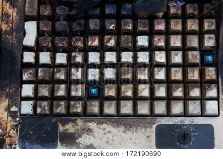 Charred and melted keyboard after the fire. Close up.
