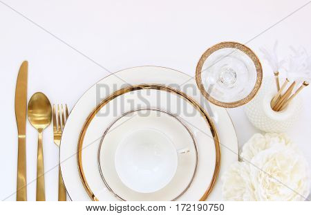 Chic and elegant white and gold dinner place setting. Open space for copy.