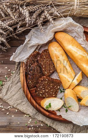Baguette, with black bread in wooden bowl on table with sunflower seeds and wheat