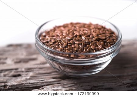 Linen seeds in a glass bowl on wooden table horizontal