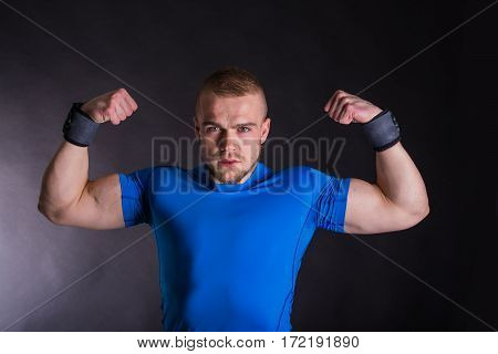 Front View Portrait Of A Young Fitness Man Standing With Arms Up Over Dark Studio Background.