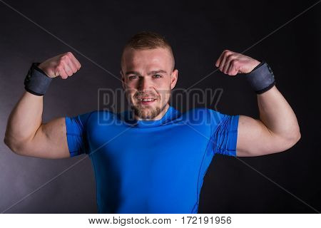 Front View Portrait Of A Smiling Young Athlete Man Standing With Arms Up Over Dark Studio Background