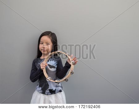 Little Asian Child Play The Tambourine, Gray Background