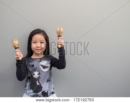Little Asian Child Play The Maracas, Gray Background