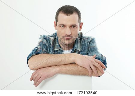 Portrait of smart serious young man in shirt sitting against white background