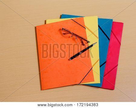 Office folders, glasses and pen on desk