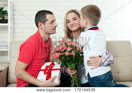 Son hiding bouquet to surprise mommy on mother's day. Woman, man child hugs and kisses