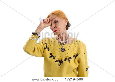 Old woman holding medicine. Sad senior lady isolated. I need some aspirin.
