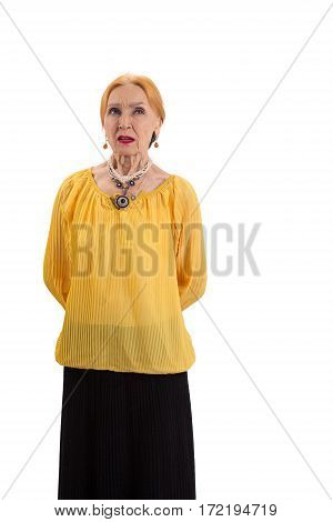 Woman with hands behind back. Pensive woman standing isolated. Doubt and wait.