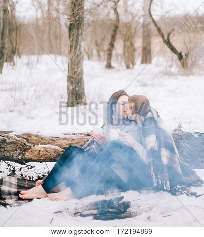 Young Woman And Man Are In Front Of Smoking Bonfire In Winter Picnic.