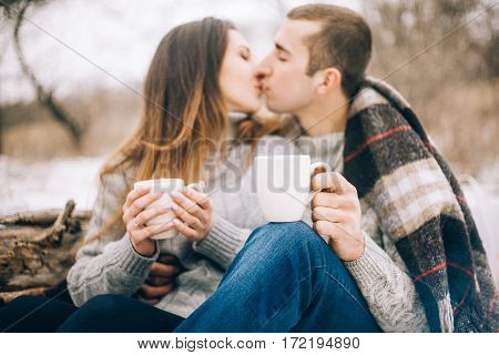 Young Woman And Man Are Kissing On Winter Picnic.