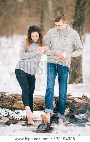 Young Woman And Man Warms Bare Feet Over Fire At Winter Picnic.