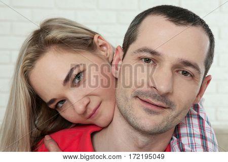 Cheerful young couple looking at camera close-up at home